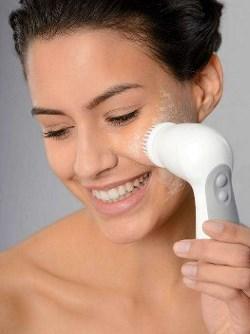 Kvinde der renser ansigtet med en elektronisk rensebørste.